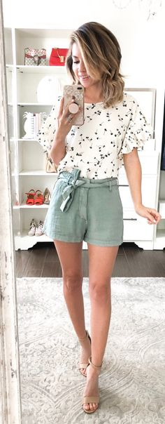#spring #outfits woman holding smartphone in front of mirror. Pic by @monicsutter