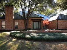 Red Brick House With A White Standing Seam Metal Roof