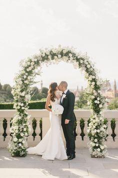 Bride and groom under a ivory and greenery wedding arch: http://www.stylemepretty.com/destination-weddings/italy-weddings/2016/08/27/an-intimate-elegant-wedding-in-florence/ Photography: Facibeni Fotografia - http://www.photographertuscany.com/
