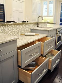 This gourmet island features a prep sink, large drawers, a single oven, and lowered marble countertops, perfect for rolling out dough.