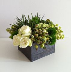 A combination of (artificial) ranunculus, viburnum, succulents, rosehip, snowberry, thistle, roses, and moss in a square wood container. The perfect size for a side table, coffee table, or night stand. This design makes a great gift! Approximately 10 wide x 10 deep x 7 tall The container alone measures 6 wide x 6 deep x 4 tall Have any questions? Not quite the right size or color? Custom orders welcome! Contact me for more information.