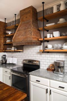 Fixer Upper - Lovely country kitchen features white cabinets adorned with oil-rubbed bronze pulls paired with gray quartzite countertops and a white subway tiled backsplash accented with gray grout flanking a stainless steel stove under barn board kitchen hood with wood and plumbing pipe shelving on either side.