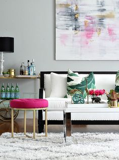 Black and white sofa with palm print pillows, Moroccan diamond shag rug, pops of pink and gold decor, and DIY abstract large scale art