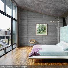 Eine riesige, wandausfüllende Fensterfront sorgt für ein maximal ausgeleuchtetes Schlafzimmer. Der Sichtbeton an Wand und Decke wirkt somit nicht düster, sondern…