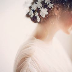 Elegant flowers in her hair. Photographed by Elizabeth Messina