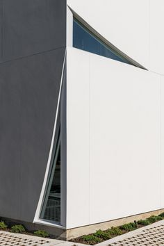 Rectangular in plan, the new building has a sculptural envelope made of white stucco panels in varying shapes. Largely opaque, the facades have angular cutouts that bring slivers of daylight into the building.