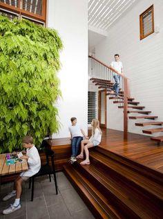 еscalier design à marches suspendues en bois et mur végétalisé