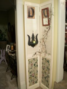 Great way to repurpose a salvaged bi-fold door! Vintage wallpaper is decoupaged on lower panels and upper louvers hold candles, mirrors, etc.  Love it!