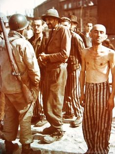 American soldiers on a tour of the infamous Buchenwald Concentration Camp at Weimar, Germany, listen to an English speaking prisoner as he tells how the S.S. guards tortured and killed some of his comrades. Many thousands of prisoners were said to have died in this room. They were hanged by their heads from the hooks around the walls and beaten to death. An elevator at the other end of the room hoisted the bodies upstairs to the crematory.