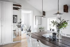 Wood and green add depth and color to this black + white space in Sweden