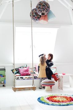 White floors, walls and furnitures. Clourful textiles. And a swing!!!