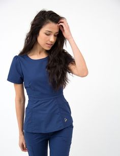The Peplum Top in Estate Navy Blue is a contemporary addition to women's medical scrub outfits. Shop Jaanuu for scrubs, lab coats and other medical apparel.