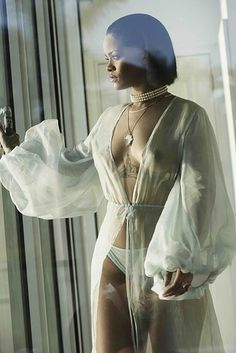 "First off, let's just talk about this outfit. Can we just acknowledge that Rihanna ""woke up"" wearing a sheer wrap and a full neck of pearls, and she is strolling around her house with a gun? 