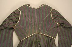 Round Gown ca. 1795; Met 1979.20a-g. Ensemble includes gown, separate stays, sleeveless spencer, and separate sleeves (probably left over from an earlier styling of the gown), all from the same striped silk satin fabric. Closer detail of spencer back. Green stripes are very slightly narrower than purple stripes. Sweat stains at the center back are more extensive than those on the gown underneath it. Conclusion: It is likely that the spencer was worn over other gowns, not this one.