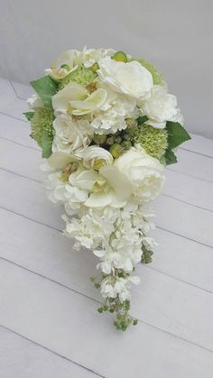 Beautiful, high quality faux floral Green / White Rose, Hydrangea bridal bouquet in Teardrop/Cascade style. Finished with double satin ribbon. Matching items and compete package options available. ALSO INCLUDES : 1 x Matching Groom Boutennaire. THIS LISTING IS FOR 1 BRIDAL BOUQUET AND GROOMS BOUTENNAIRE - matching items and packages can be found in the store.   Ribbon color or flower selection on all wedding bouquets can be customized upon request. These bouquets are much more durab...