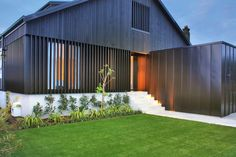 dark stain vertical cedar cladding, vertical metal cladding to front section of building