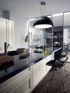 The central counter with sink and hob, the group of wall units with low cabinet and the block of cupboards and tall units with ovens, styled to form an attractive contemporary kitchen.