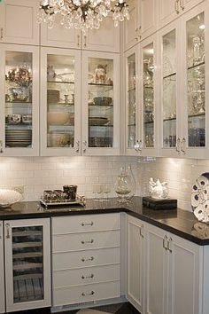 glass cabinet doors with glass shelves and lighting inside! Under cabinet lighting as well, and cupboards way up high in the soffit!