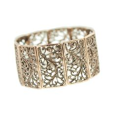 An antiqued copper bracelet features an elegant filigree design. The wide stretch bracelet hugs your wrist perfectly while its smooth polished frame gives it a modern appeal. The delicate swirled filigree brings out a vintage touch.  This is a charming addition to your jewelry collection.
