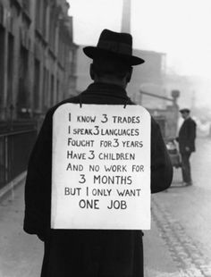 1935    A man makes his own protest sign against unemployment.