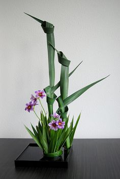flower arrangement: Ikebana 'Cranes standing in the reeds' . Alliaceae with Yucca leaves . like the knotting in the Arrangement Ikebana Arrangements, Creative Flower Arrangements, Ikebana Flower Arrangement, Floral Arrangements, Art Floral, Deco Floral, Floral Design, Design Art, Flower Show