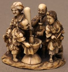 Ivory netsuke depicting a family group of seven, five stood on land one of which is pounding linen, and one being a child holding its nose. Other two figures are kneeling washing clothes in the river.