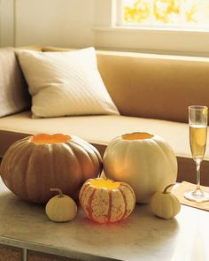 If the thought of a cadre of frightful jack-o'-lanterns gives you the chills, opt for a lovely and luminous group of votive holders instead. These gently glowing lights, cut from pumpkins in pale hues, are easy to make: Simply slice off the tops, and scoop off the flesh.