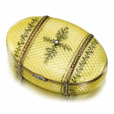 A FABERGÉ JEWELLED ENAMEL BOX, MOSCOW, 1899-1908 oval, the surface enamelled in translucent lemon yellow over wavy engine-turning, the lid centred with a rose-cut diamond within dendritic tendrils, bound with chased two-colour gold laurel bands and painted leaf and berry borders, diamond-set thumbpiece, gilt interior, with K Fabergé in Cyrillic beneath the Imperial Warrant and Cyrillic initials KF, 84 standard.