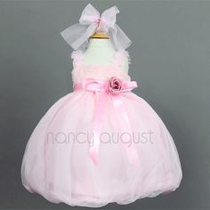 Tulle Baby Dress in Pink: This dainty little pink number is for that dazzling little bundle of joy of yours! Making the beautiful ballerina trend more approachable and wearable, this pink tulle overlay dress incorporates a trendy and chic bodice with ruffled straps enhanced with beautiful mesh ribbons and a full yet fun bubble skirt. To finish the look is an adjustable satin waist ribbon adorned with a detachable flower in the front and tulle sashes in the back.
