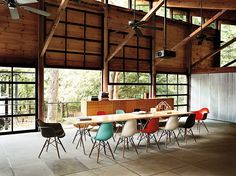 Eames Molded Plastic Chairs add a little pop in palette to this voluminous industrial workspace.