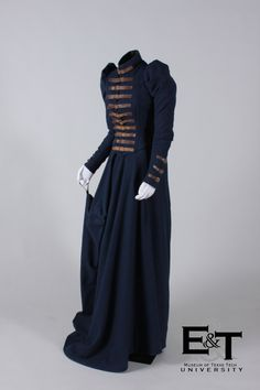 1870s Two-Piece Navy, Wool Riding Habit,  Museum of Texas Tech University has a fitted bodice, pointed in the center front and has a bodice opening which fastens with brown leather, buckled straps in the front.  The high-standing collar, sleeve cuffs and squared tails in the back are also trimmed and fastened with the buckled leather straps.  The long-trained skirt has two gores; an unusual cut with an inset that cups to allow space for fitting over the saddle.