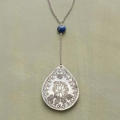 LAPIS LOTUS NECKLACE - A lotus, hand-stamped on a pendant necklace of sterling silver, symbolizes new beginnings as a lightly faceted lapis, blue as the midnight sky, hovers above.