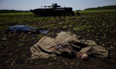 Bodies covered with blankets lie in a field near the village of Blahodatne, after at least 11 Ukrainian troops were killed and 30 others were wounded when Pro-Russians attacked a military checkpoint, the deadliest raid in the weeks of fighting in eastern Ukraine.  Photograph: Ivan Sekretarev