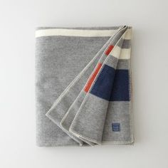 "Soft, military inspired wool blanket with blue / orange / white stripe end details. With over a century of experience, Faribualt Woolen Mill Co. uses the highest quality materials, manufacturing, and hand sewn techniques.    • whipstitch edge detailing  • dimensions: 90"" x 72""  • 100% virgin wool  • made in USA#p_SWO-bGBALluD"