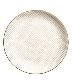 White. Porcelain plate with a gold-colored, graphic pattern. Diameter 10 1/2 in.
