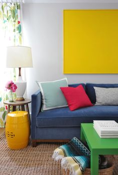Colorful living room features yellow art over blue velvet sofa paired with seafoam green pillow, red pillow and gray lumbar pillow next to white and gold vintage lamp on round end table as well as green parsons coffee table over jute rug.