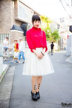 Student Bei is wearing a resale red turtleneck sweater, which she paired with an off-white tulle skirt. Completing her ensemble are tattoo stockings and Jeffrey Campbell platform booties. Her accessories include a resale cream shoulder bag and Utopica wood bangles and pearl earrings.