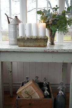 Simple white pillar candles in a decorative container with moss or greens around the base