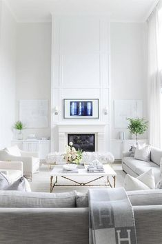 Vancouver home with all white color scheme + millwork on the fireplace + custom paneling on the fireplace with built in base cabinetry on either side of the fireplace + brass coffee table legs with a white marble top Fireplace Built Ins, White Fireplace, Fireplace Remodel, Living Room With Fireplace, Fireplace Design, Fireplace Accent Walls, Two Story Fireplace, Custom Fireplace, Fireplace Wall