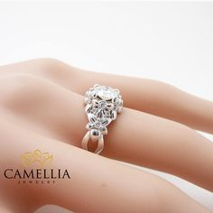 This natural diamond floral engagement ring makes an amazing gift for the woman in your life whether a wife, friend or mother. It features a 14K white gold diamonds encrusted floral band with forever brilliant moissanite center. This art nouveau styled ring is the perfect balance of style and grace. It can be worn as a modern fashion statement or as a promise ring for the life that is yet to come. This is a limited edition Camellia Jewelry original. Order now to guarantee availability…
