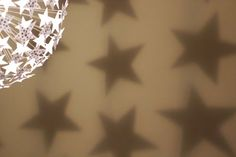 Ikea Maskros Lamp - remove flowers and use stars - which will project star shadows on the wall (link contains link for template)