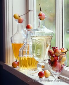 Crab apples are used as stoppers for a pair of glass decanters on this window sill