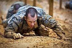 U.S. Army Soldiers from the One Station Unit Training (OSUT) low crawl while negotiating an obstacle course during their first week of Basic Training in Ft. Benning, Ga. March 9, 2012. OSUT is a training program in which recruits remain with the same unit for both Basic Combat Training (BCT) and Advanced Individual Training (AIT).