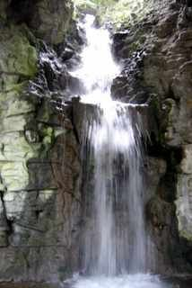 cascades in a 32 meter waterfall, falling into a large cave of 20 meters in height and decorated with artificial stalactites