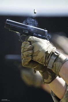 A gunner with 7 Force Protection (FP) Wing, RAF Regiment fires a Sig Sauer P226 pistol on a firing range.
