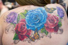 Μια συμμετέχουσα στην Μεγάλη Βρετανική επίδειξη τατουάζ του Λονδίνου ποζάρει με τα διάστικτα άνθη και πεταλούδες που φέρει ανάλαφρα στην πλάτη.