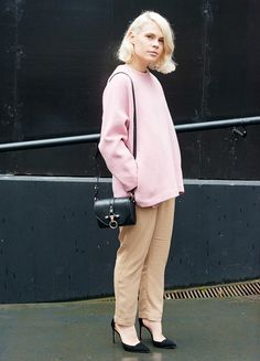 A pink oversized sweater is paired with camel trousers, black pointed toe heels and a black bag.