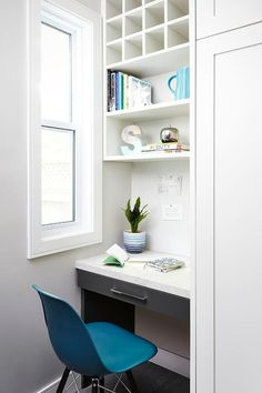 Chic, small office features a charcoal gray lacquered desk paired with a bright blue eames Molded Plastic Chair tucked under a white pigeon hole storage unit and stacked shelves.