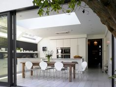 Modern Kitchen extension white wood floor, sliding glass doors, LEM bar stool and white corian worksurfaces