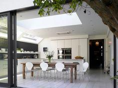 Modern Kitchen extension white wood floor, sliding glass doors, LEM bar stool and white corian worksurfaces